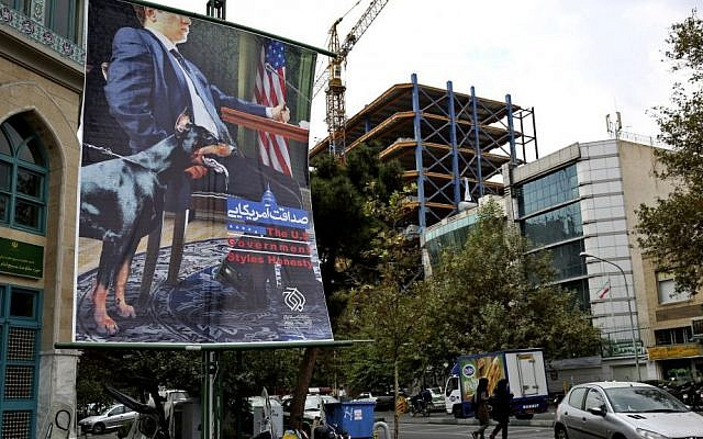 A poster depicting an American negotiator wearing a suit jacket and tie at a negotiating table and a dog to his side is displayed in Palestine square, Tehran, Iran, Sunday, Oct. 27, 2013. (Photo credit: AP/Ebrahim Noroozi)