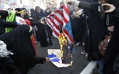 Iranian female demonstrators burn a representation of the US flag and a caricature of President Barack Obama in an annual state-backed rally in front of the former US Embassy in Tehran, Iran, in November 2012. (photo credit: AP/Vahid Salemi/File)