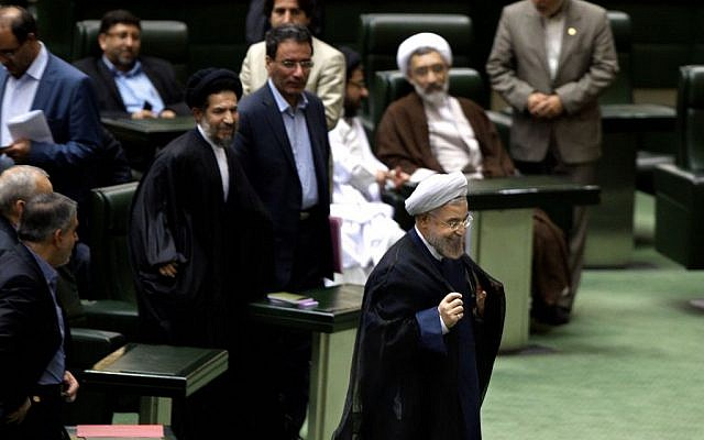 Iranian President Hassan Rouhani, center, leaves at the end of a session of parliament in Tehran, Iran, Sunday, Oct. 27, 2013. (photo credit: AP)