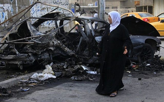 A woman inspects the site of a deadly car bomb attack that killed her sister, in Baghdad, Iraq, October 2013 (photo credit: AP/Hadi Mizban)
