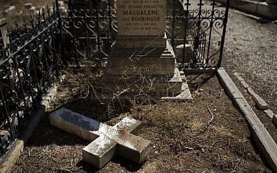 In this Monday, Oct. 7, 2013 photo, a damaged grave after a vandal attack is shown in the Protestant Cemetery of Mt. Zion, Jerusalem. (Photo credit: AP/Bernat Armangue)