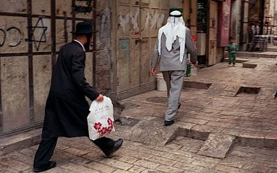 In this June 12, 1997 file photo, an Orthodox man walks behind a Palestinian man on a street in the walled Old City of Jerusalem. (photo credit: AP/Greg Marinovich, File)