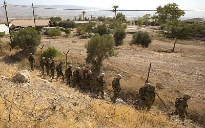 Troops combing the area next to the Brosh Habika vacation village Friday. (photo credit: AP/Sebastian Scheiner)