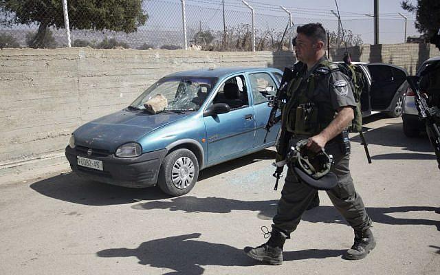 An Israeli policeman walks by a damaged car inside a schoolyard in the West Bank village of Jaloud, near Nablus, Wednesday, October 9, 2013. (photo credit: AP/Nasser Ishtayeh)