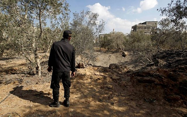 A member of Hamas inspects the damage following an Israeli air strike in Gaza City on Monday, Oct. 28, 2013. (photo credit: AP/Hatem Moussa)