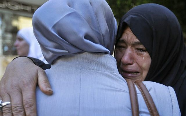 A Syrian refugee in Beirut says goodbye to a relative at the International Organization for Migration office before some refugees board a bus to Beirut International Airport for a flight to Germany, after being accepted for temporary resettlement. (AP/Hussein Malla)