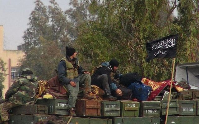 Rebels from the al-Qaeda affiliated Jabhat al-Nusra sit on a truck full of ammunition, at Taftanaz air base, which was captured by the rebels, in Idlib province, northern Syria in 2013 (photo credit: AP/Edlib News Network, ENN)