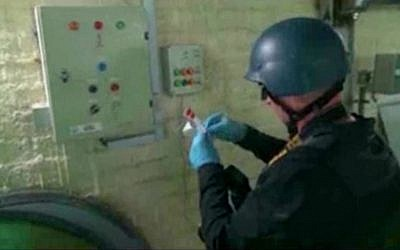 Video broadcast on Syrian State Television purports to show an UN expert examining a chemical weapons plant at an unknown location in Syria, October 8, 2013 (AP/Syrian State Television)