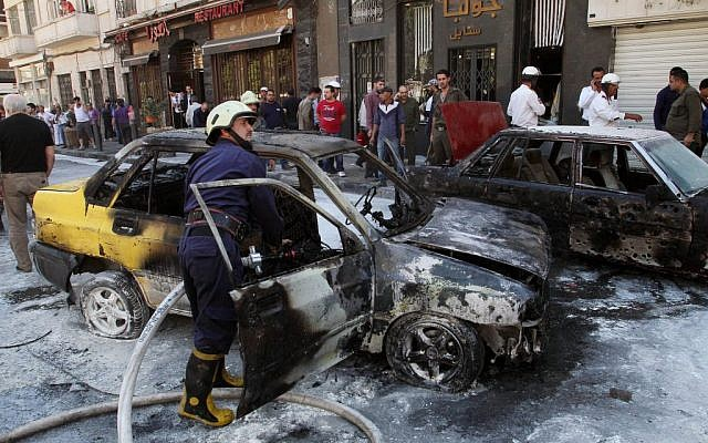 Firefighters extinguish a burning vehicle after two mortar rounds struck the Abu Roumaneh area in Damascus, Syria, Saturday, Oct. 12, 2013. (Photo credit: AP)