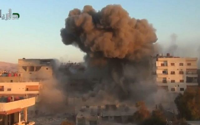 Illustrative photo of smoke billowing amid buildings in Daraya, near Damascus, Syria, on Tuesday, October 15, 2013. (photo credit: AP/Shaam News Network via AP Video)
