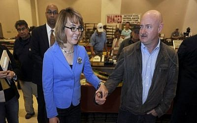 Former Arizona congresswoman Gabrielle Giffords, left, and her husband Mark Kelly tour the New EastCoast Arms Collectors Associates arms fair in Saratoga Springs, N.Y. on Sunday, Oct. 13, 2013. (photo credit: AP Photo/Tim Roske, Pool)