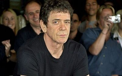 In a June 24, 2003 photo, Lou Reed has his hands imprinted as supporters cheer in the background as he is inducted into Hollywood's Rockwalk, in the Hollywood section of Los Angeles. (Photo credit: AP Photo/Ric Francis, File)