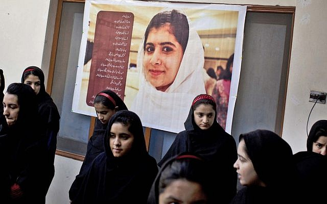 In this Thursday, November 15, 2012 photo, Pakistani girls gather under a poster of Malala Yousufzai in her old school in Mingora, Swat Valley, Pakistan. The giant poster of her that once emblazoned the wall of the assembly hall has since been removed. (photo credit: AP Photo/Anja Niedringhaus)