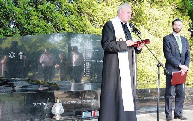 The local priest and rabbi in the Bezeq-sponsored ceremony in Miedzna in July. (photo credit: courtesy)