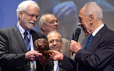 Dr. John Donoghue (L.) accepts a $1 million award from former president Shimon Peres at the BrainTech event in Tel Aviv, October 15, 2013. The award was presented to  Donoghue and his team for their work in using brain tech to treat degenerative brain diseases (Photo credit: Chen Galili)