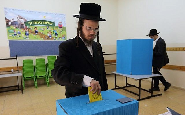 An ultra-Orthodox man votes at a polling station during Israel's municipal elections, October 22, 2013. (photo credit: Yaakov Naumi/Flash90)
