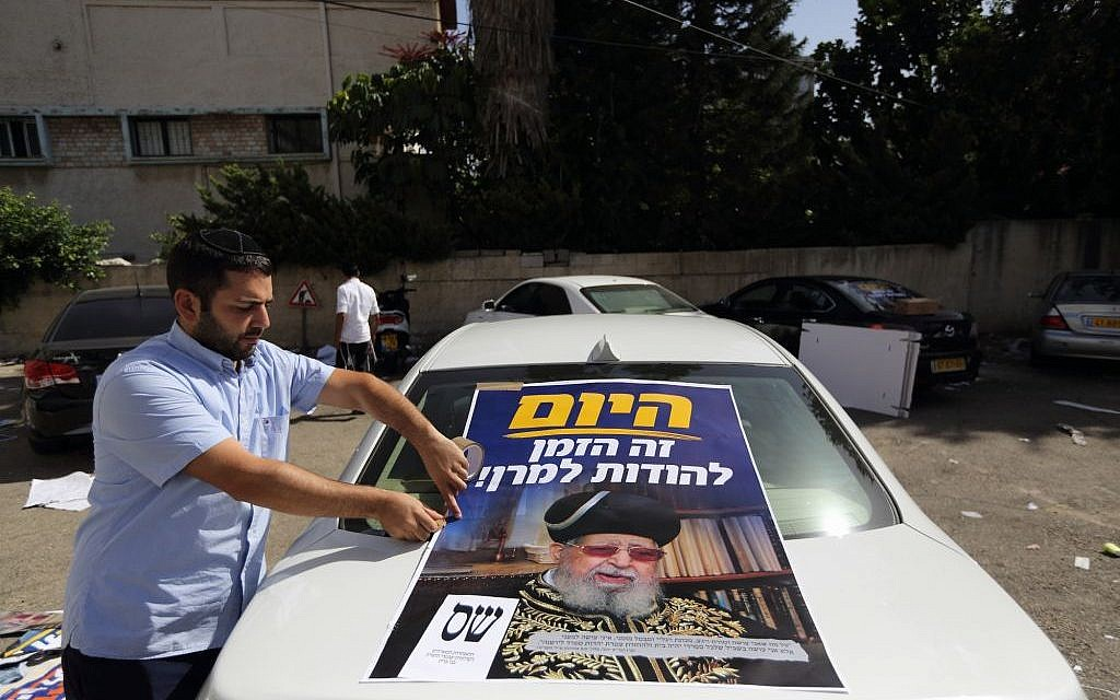 A man attaching a poster with a picture of Rabbi Ovadia Yosef to his car in Bnei Brak Tuesday. (photo credit: Yaakov Naumi/Flash90)