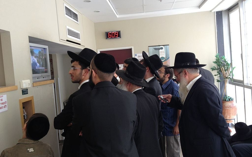 Followers of Rabbi Ovadia Yosef watch the television news to learn of his condition while waiting at the hospital where he was being treated shortly before he died, October 7, 2013. (photo credit: Mitch Ginsburg)