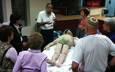 Baruch Bloom, in white shirt, a board member of Kavod v'Nichum, demonstrates how to prepare a body for burial at the organization's 2012 conference in Los Angeles. (photo credit: JTA)