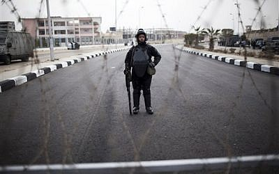 A riot policeman stands guard behind barbed wire outside of a police academy compound were the trial of ousted President Mohammed Morsi will be held in Cairo, Egypt, Monday, Nov. 4, 2013. (photo credit: AP Photo/Manu Brabo)