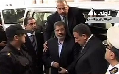 This image made from video broadcast on Egyptian State Television shows ousted President Mohammed Morsi arriving for a court hearing at a police academy compound in Cairo, Egypt, Monday, Nov. 4, 2013. (photo credit: AP Photo/Egyptian State Television via AP video)