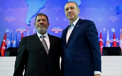 In this Sunday, Sept. 30, 2012 file photo provided by Turkish Prime Minister's Press Service, Turkey's Prime Minister Recep Tayyip Erdogan, right, and then-Egyptian president Mohammed Morsi salute the members of Turkey's ruling Justice and Development Party in Ankara, Turkey (photo credit: AP/Kayhan Ozer)