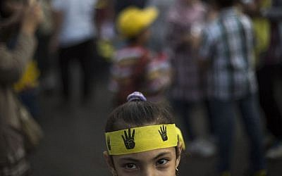 An Egyptian girl attends a protest by supporters of Egypt's ousted president Mohammed Morsi, in Nasr City in Cairo, Egypt, Friday Nov. 1, 2013. Her headband bears the four-fingered emblem which has become a symbol of the Rabiah al-Adawiya mosque, where Morsi supporters held a sit-in for weeks that was violently dispersed in August. (AP Photo/Manu Brabo)