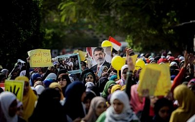 Supporter of Egypt's ousted president Mohammed Morsi  protest a day before the trial of the former president, in Cairo, Egypt, on Sunday, November 3, 2013. (photo credit: AP/Eman Helal)