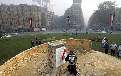 """A woman holds a poster of Egyptian Defense Minister Gen. Abdel-Fattah el-Sissi which reads, """"we authorize you,"""" as she stands at the foundation for a future memorial to protesters killed in the country's uprising more than two-and-a-half years of turmoil, after it was damaged in Tahrir Square, Cairo, Egypt, on Tuesday, November 19, 2013. (photo credit: AP Photo/Amr Nabil)"""