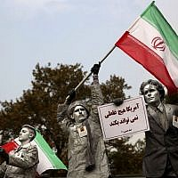 "Iranian artists hold posters with Persian that reads,'""America cannot do a damn thing,' as they perform during an annual anti-American demonstration in Tehran, Iran, Monday, Nov. 4, 2013 (photo credit: AP/Ebrahim Noroozi)"