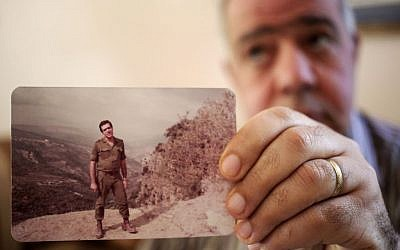 Assaad Chaftari, once deputy chief in the intelligence service of the Lebanon's feared Lebanese Forces militia, shows his picture with the military form of the Christians' Lebanese Forces militia, during an interview on Sept. 22, 2013. (photo credit: AP/Hussein Malla)