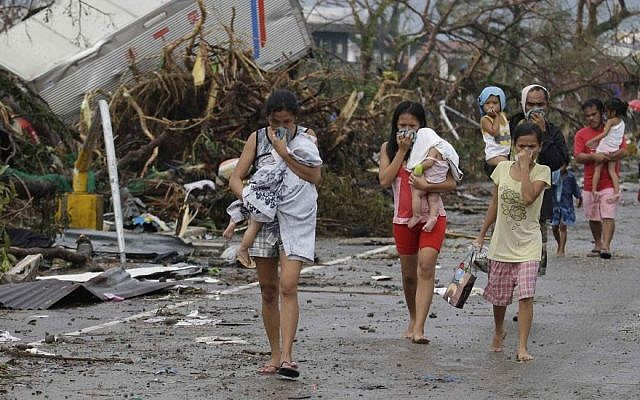 Residents cover their nose from the smell of dead bodies in Tacloban city, Leyte province central Philippines on Sunday, Nov. 10, 2013. Typhoon Haiyan, one of the strongest storms on record, slammed into six central Philippine provinces Friday leaving a wide swath of destruction and hundreds of people dead. (Photo credit: AP/Bullit Marquez)