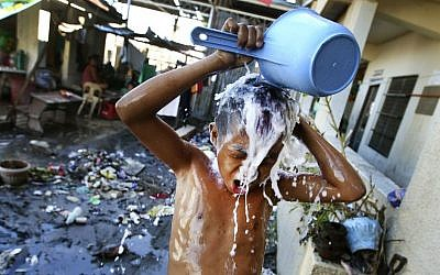 A young Filipino takes a shower at a school turned into a temporary shelter for those affected by Typhoon Haiyan, in Tacloban, Philippines, Monday, November 18, 2013 (photo credit: AP/Dita Alangkara)