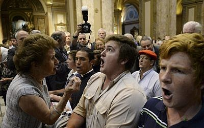 A woman attending a ceremony that marked Kristallnacht and the beginning of the Holocaust, left, tries to stop ultra-traditionalist Catholics from interrupting the interfaith event at the Metropolitan Cathedral in Buenos Aires, Argentina,  Nov. 12, 2013. (photo credit: AP/Rodolfo Pezzoni,DyN)