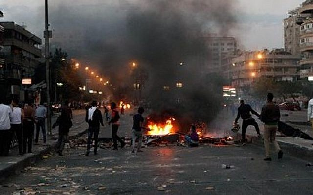 Protesters throw rocks at supporters of the Muslim Brotherhood in the Nasr City district in Cairo, Egypt, Friday, Nov. 22, 2013 (photo credit: AP/El-Shorouk newspaper, Sabry Khaled)