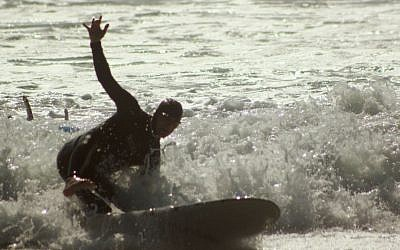 Rabbi Eliyahu Fink tries to catch a wave during the filming of an episode of 'Church Rescue'. (photo credit: Courtesy of T Group Productions)