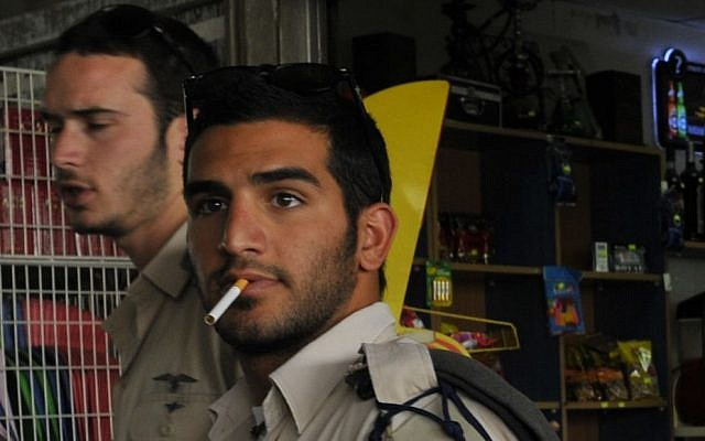 An Israeli soldier smokes a cigarette at the Beersheba central bus station (photo credit: Serge Attal/Flash90)