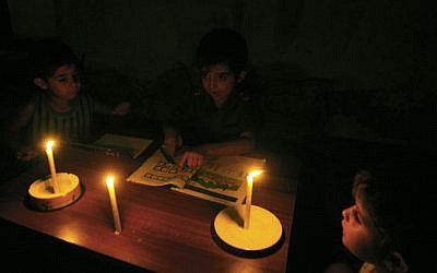 Palestinian children do their homework by candlelight in their family home during a power cut in the Rafah refugee camp in the southern Gaza Strip on September 18, 2013. (photo credit: Abed Rahim Khatib/Flash90)
