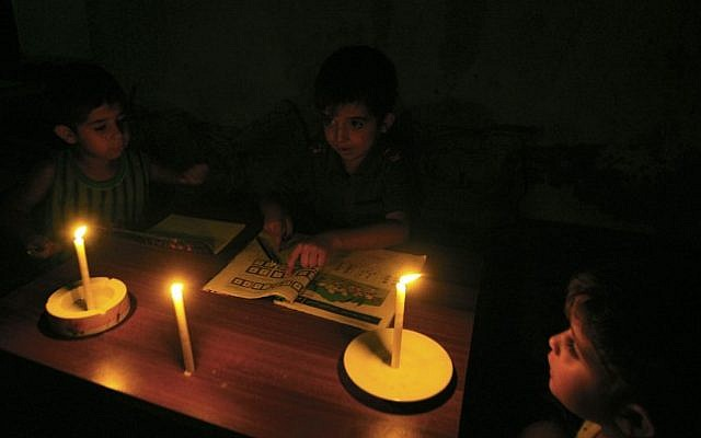 Palestinian children do their homework by candlelight in their family home, during a power cut in the Rafah refugee camp in the southern Gaza Strip, on September 18, 2013. (Abed Rahim Khatib/Flash90)
