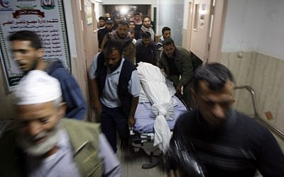 Palestinians gather around the body of a Hamas terrorist at a hospital in Khan Younis in the southern Gaza Strip October 31, 2013.  (Photo credit: Abed Rahim Khatib/Flash 90