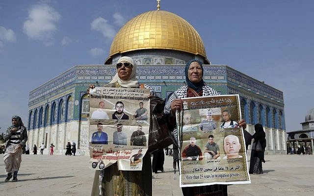 Palestinian women hold pictures of sick Palestinian prisoners held in Israeli jails outside the Dome of the Rock during a demonstration in solidarity with Palestinian prisoners held in Israeli jails. November 1, 2013 (photo credit: Sliman Khadr/Flash90)