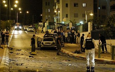 Bomb squad police unit examine the blackened remains of a car that exploded in a suspected bombing in the southern city of Ashkelon, Saturday night, November 2, 2013. (photo credit: David Buimovitch/Flash90)