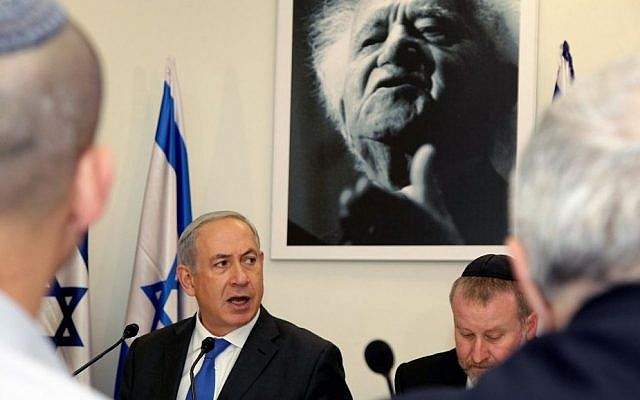 Prime Minister Benjamin Netanyahu sits under a portrait of the first Israeli prime minister David Ben-Gurion as he speaks during a special cabinet meeting at the Sde Boker academy to mark 40 years since Ben-Gurion's death. November 10, 2013. (Edi Israel/Pool/Flash90)