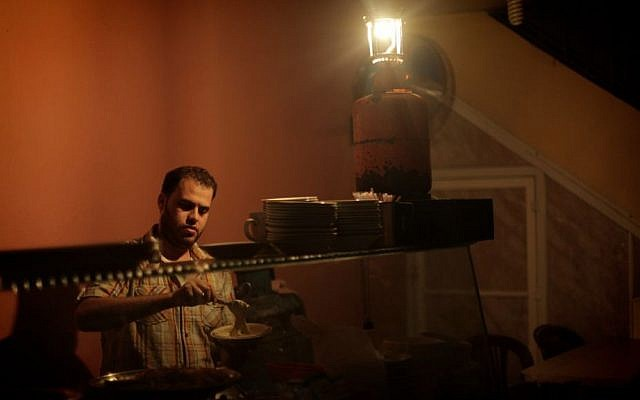 A Palestinian uses a gas lighter while he works inside his restaurant during a power outage in the Gaza Strip, November 17, 2013. (Emad Nassar/Flash90)