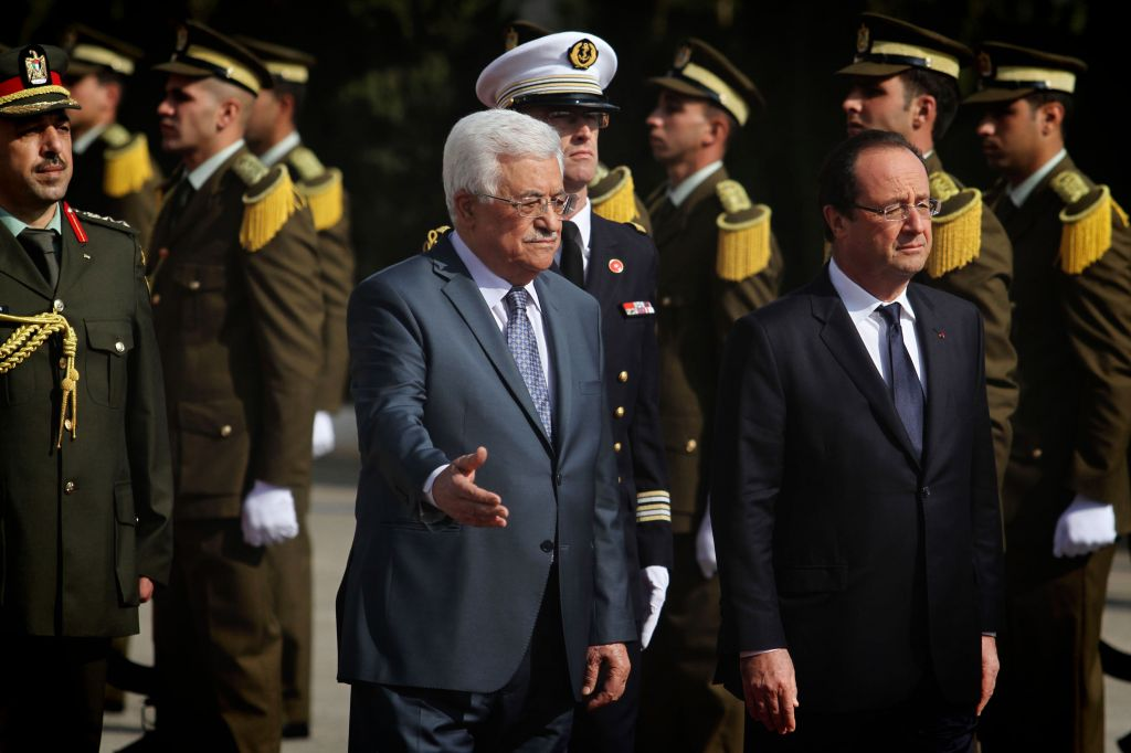French President Francois Hollande and Palestinian Authority President Mahmoud Abbas walk by a Palestinian honor guard at a welcoming ceremony in Hollande's honour, in the West Bank city of Ramallah, Monday, November 18, 2013 (photo credit: Issam RImawi/Flash90)