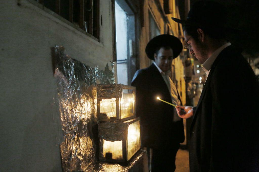 Lighting chanukiyot outdoors in Mea Shearim in Jerusalem (photo credit: Miriam Alster/Flash 90)