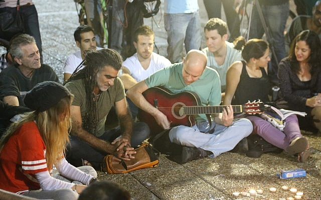Dozens of Israelis, among them singer Mosh Ben-Ari (center, with dreadlocks), light candles and sing on Rabin Square in Tel Aviv, while mourning the death of Israeli singer-songwriter Arik Einstein, who passed away at the age of 74 on November 27, 2013 (photo credit: Flash90