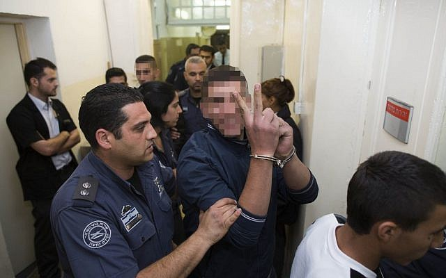 Two of the suspects alleged to have thrown stones at the car that left 2-year-old Avigail Ben Zion moderately wounded are escorted by police in the Magistrate's Court in Jerusalem, November 29, 2013. (Photo credit: Yonatan Sindel/Flash90)