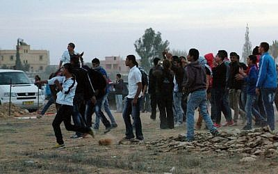 Police and protesters clash at a rally where around 1,200 demonstrators gathered in the southern Israeli town of Hura during a protest against the government's plan to resettle some 30,000 Bedouin residents of the Negev desert. The demonstrations were organized as part of an International Day of Rage against the Law for Arranging Bedouin Settlement in the Negev, known as the Prawer-Begin Plan. November 30, 2013. (Photo credit: FLASH90)
