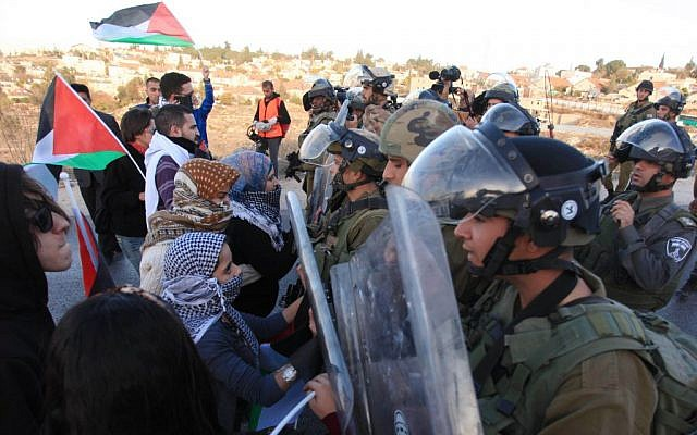 Israeli soldiers clash with Palestinian protesters outside the Jewish settlement of Beit El, near the West Bank city of Ramallah, during a demonstration against the Israeli government's plan to resettle some 30,000 Bedouin residents of the Negev desert, on November 30, 2013. (photo credit: Issam RImawi/ Flash90)